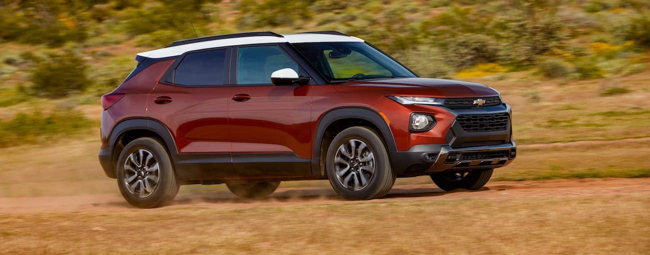 A red and white 2021 Chevy Trailblazer is driving on a trail past dry grass after winning the 2021 Chevy Trailblazer vs 2020 Chevy Trax comparison.