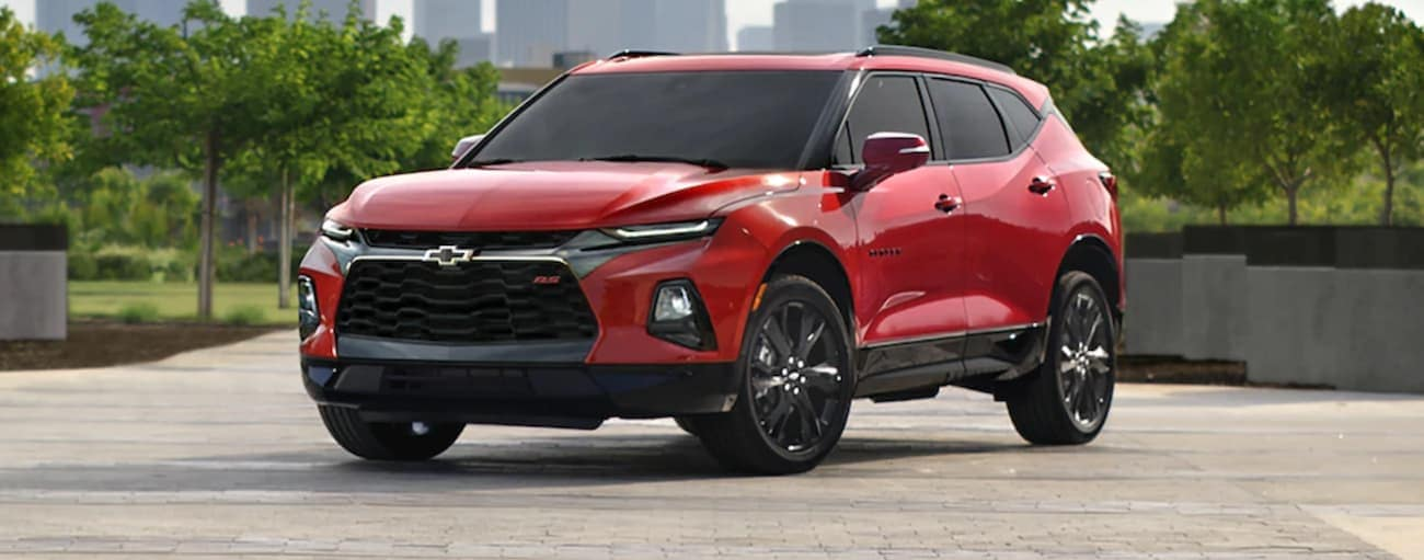 A red 2020 Chevy Blazer is parked in front of trees and a city in the distance after winning the 2020 Chevy Blazer vs 2020 Nissan Murano comparison.