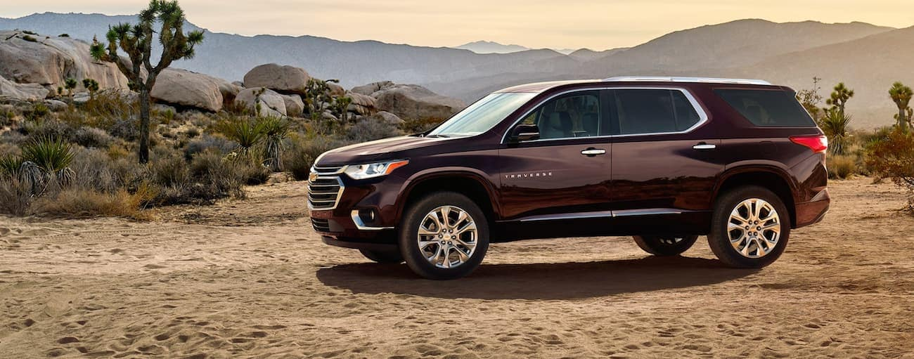 A burgundy 2020 Chevy Traverse is parked in the desert with distant mountains.