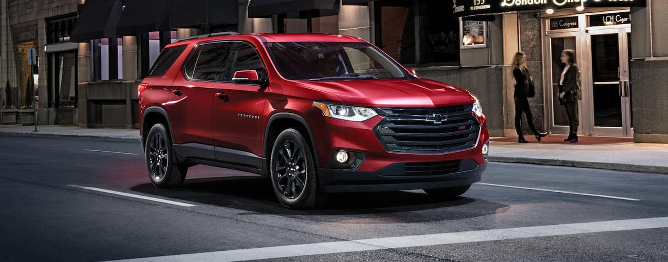 A red 2020 Chevy Traverse is stopped at an intersection on a city street at night after winning the 2020 Chevy Traverse vs 2020 Dodge Durango comparison.