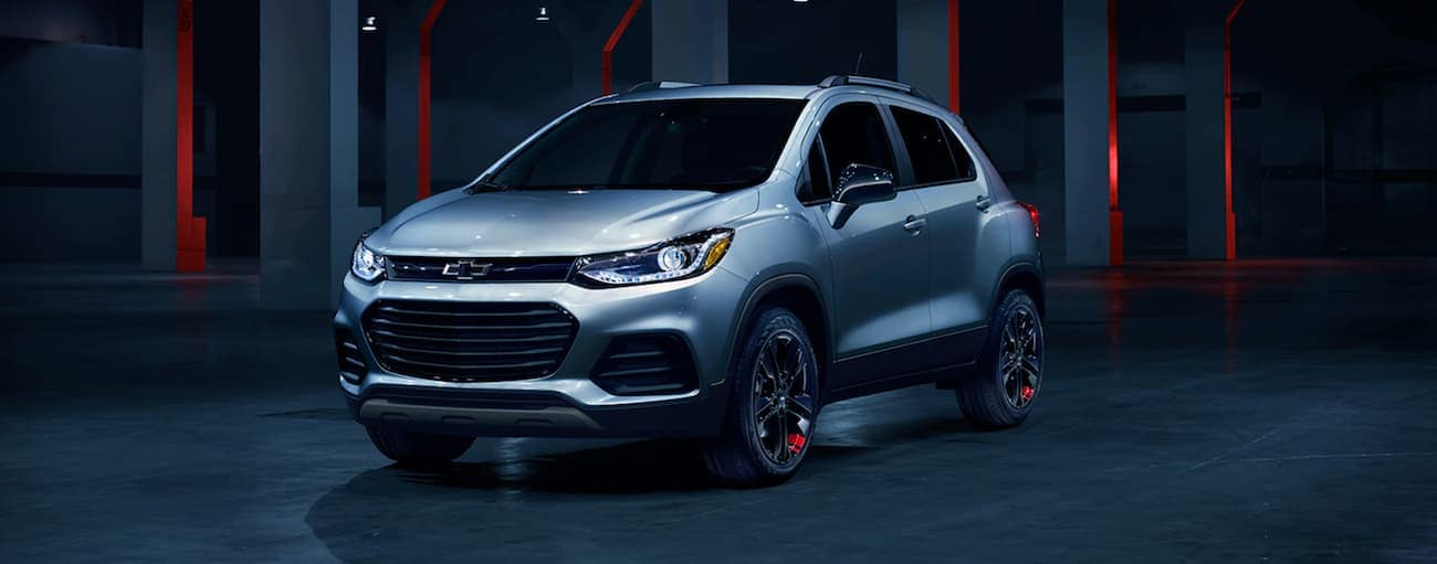 A silver 2020 Chevy Trax is in a dark showroom after winning the 2020 Chevy Trax vs 2020 Mazda CX-3 comparison.