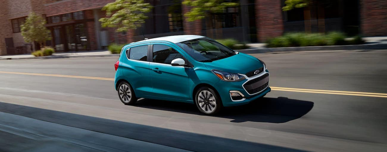 A blue and white 2021 Chevy Spark is driving on a city street near Buford, GA.