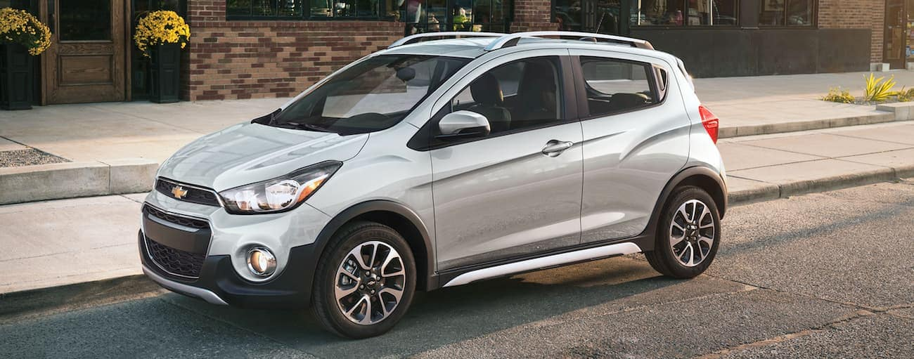 A silver 2021 Chevy Spark is parked on a city street.