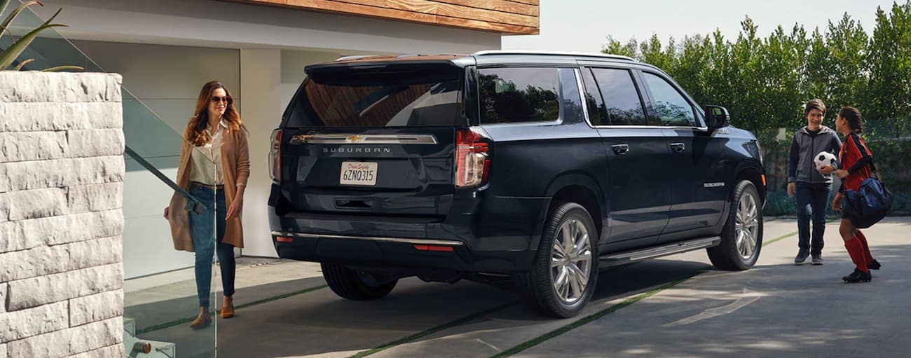 A dark blue 2021 Chevy Suburban is parked outside of a Buford home with a family walking by it.