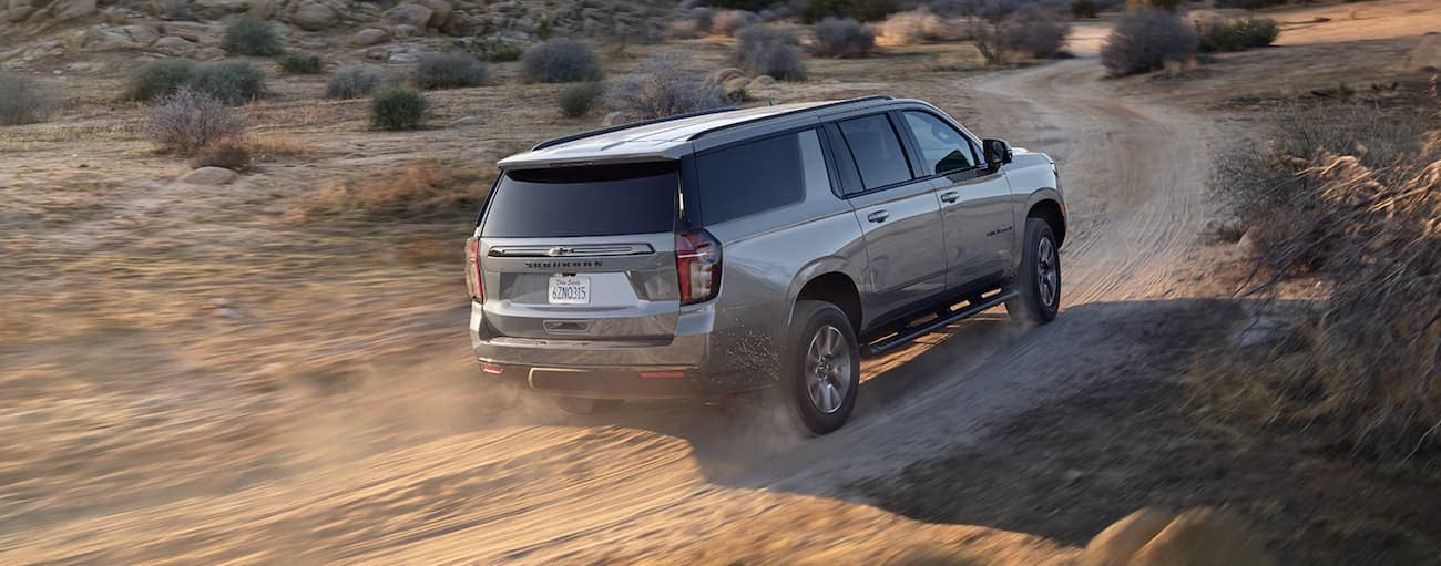 A grey 2021 Chevy Suburban is driving on a dirt road.