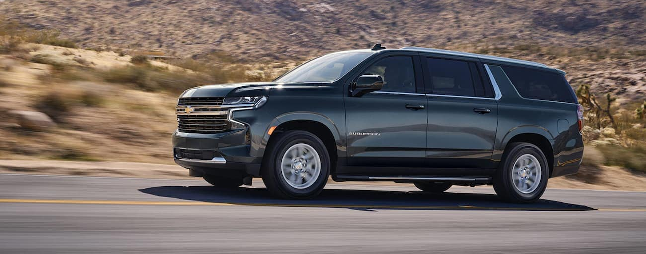 A dark grey 2021 Chevy Suburban, which wins when comparing the 2021 Chevy Suburban vs 2021 Cadillac Escalade, is driving past hills and shrubs near Buford, GA.