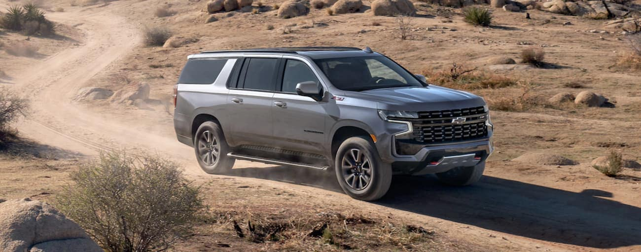 A silver 2021 Chevy Suburban is driving on a dirt road in the desert.