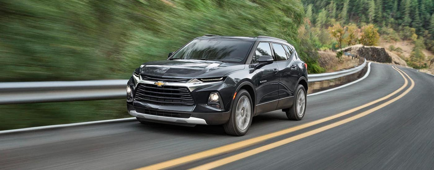 A black 2021 Chevy Blazer is driving on a highway.
