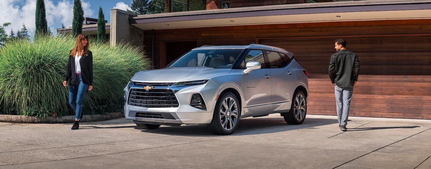 A couple is walking around a silver 2021 Chevy Blazer that is parked in front of a modern home.