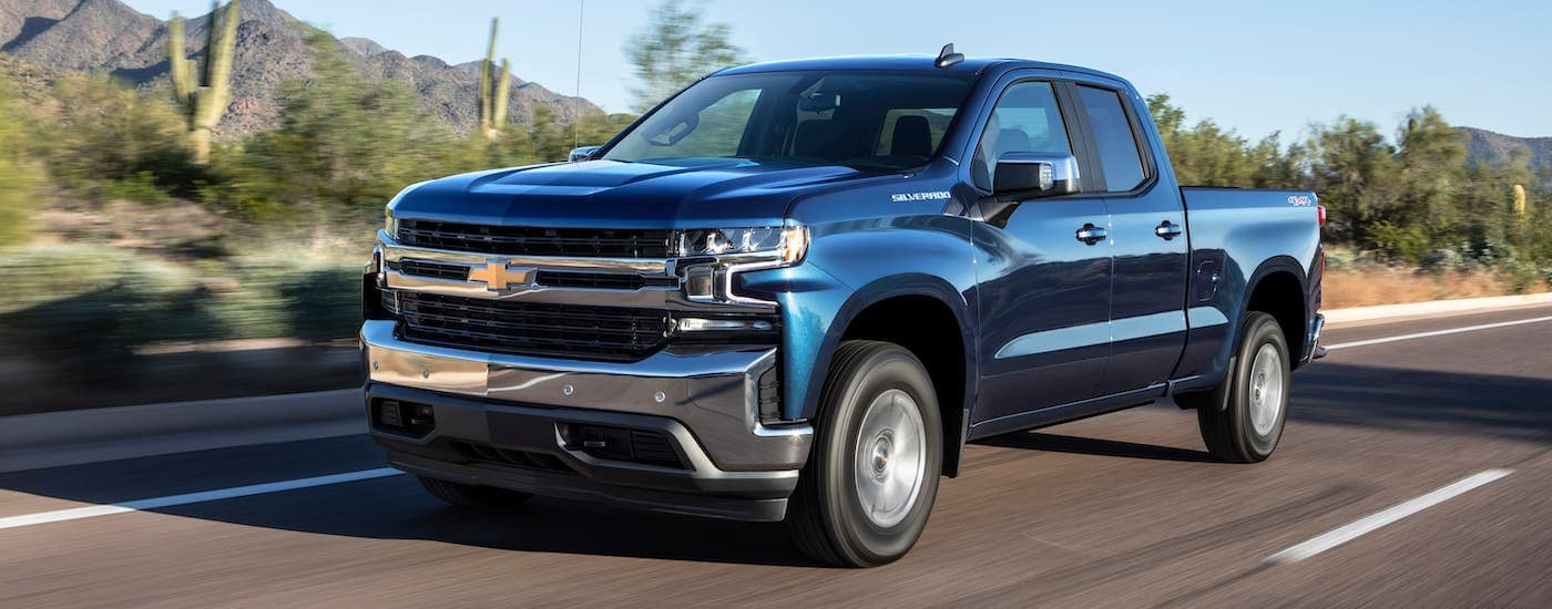 A blue 2021 Chevy Silverado 1500 RST is driving on a highway.
