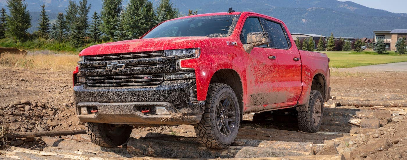 A red 2021 Chevy Silverado 1500 TrailBoss is driving on a trail and covered in mud.