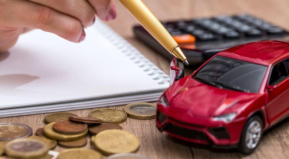 A woman is opening the door of a red toy car with the tip of a pen.