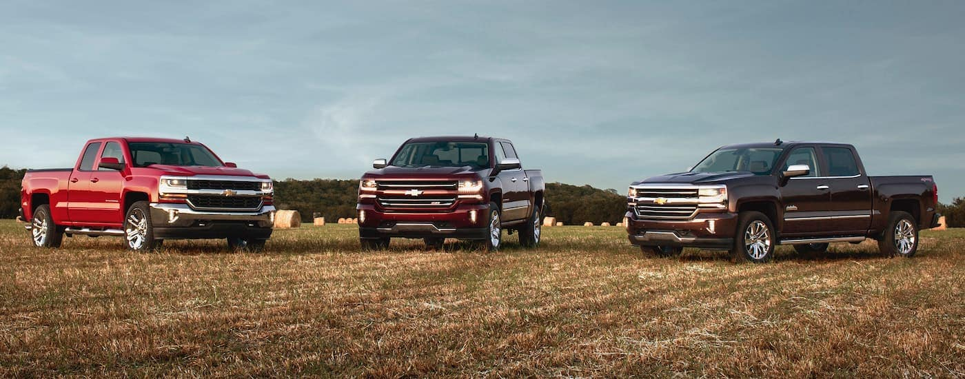 Three red 2016 Used Chevy Silverados are parked in a field.