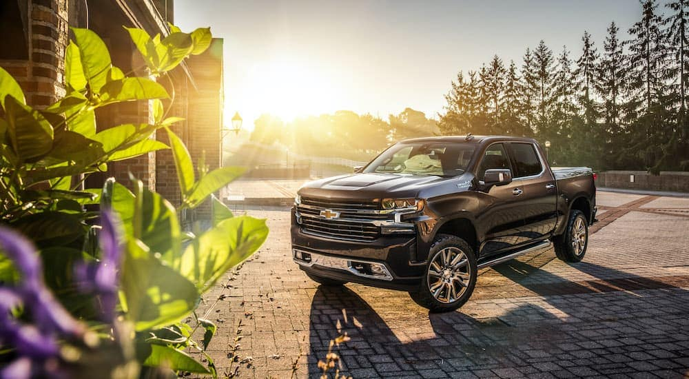 A black 2018 used Chevy Silverado is parked in a driveway at sunset.
