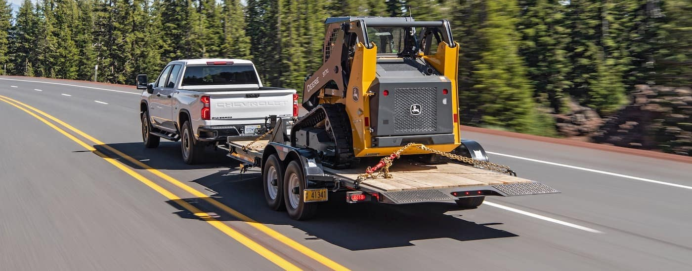 A white 2020 Used Chevy Silverado 2500HD is towing construction equipment past pine trees.