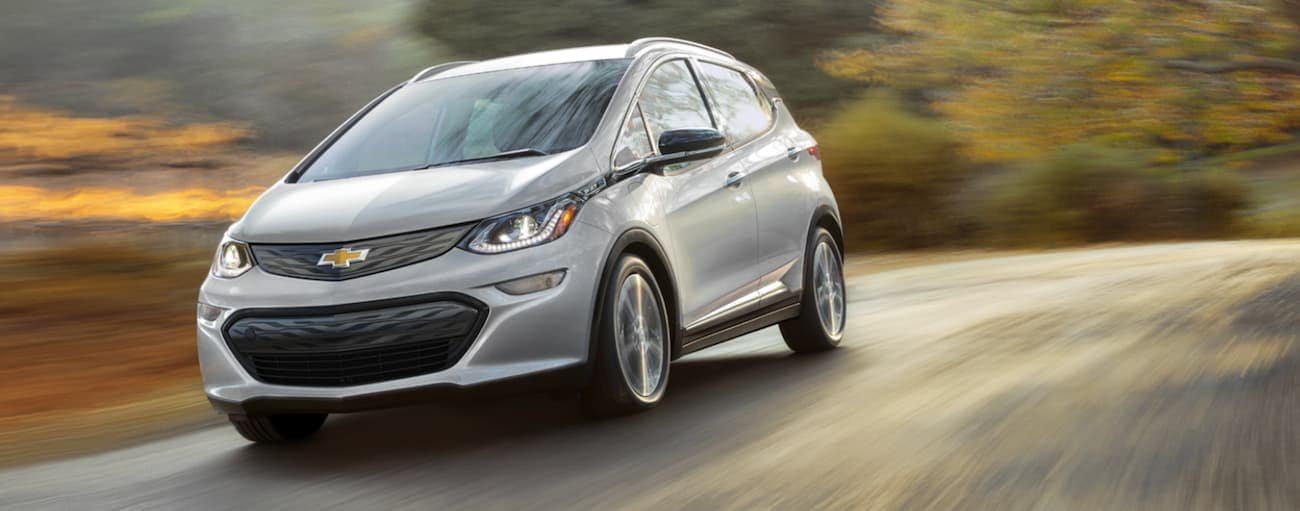 A silver 2021 Chevy Bolt EV is driving past blurred trees.