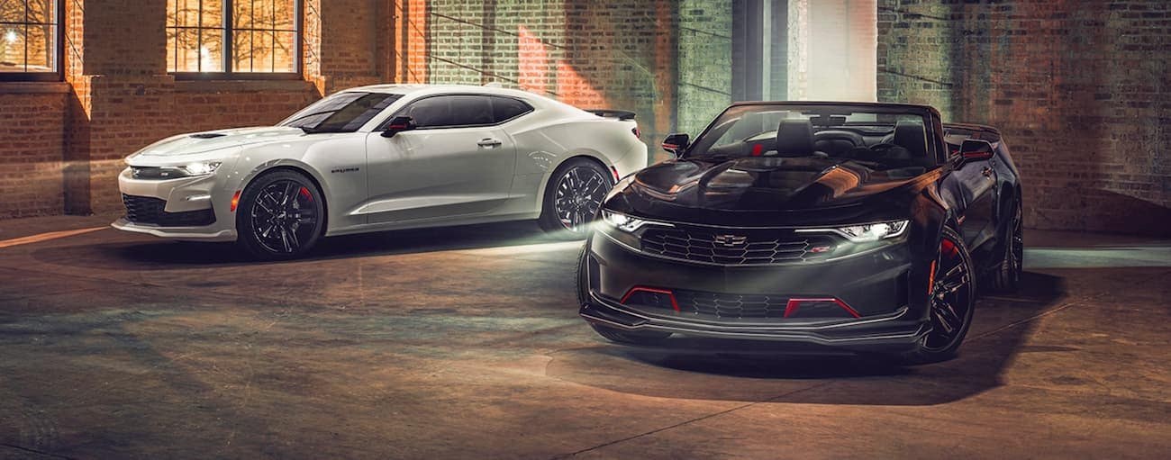 A black and a white 2021 Chevy Camaro are parked in a brick warehouse.