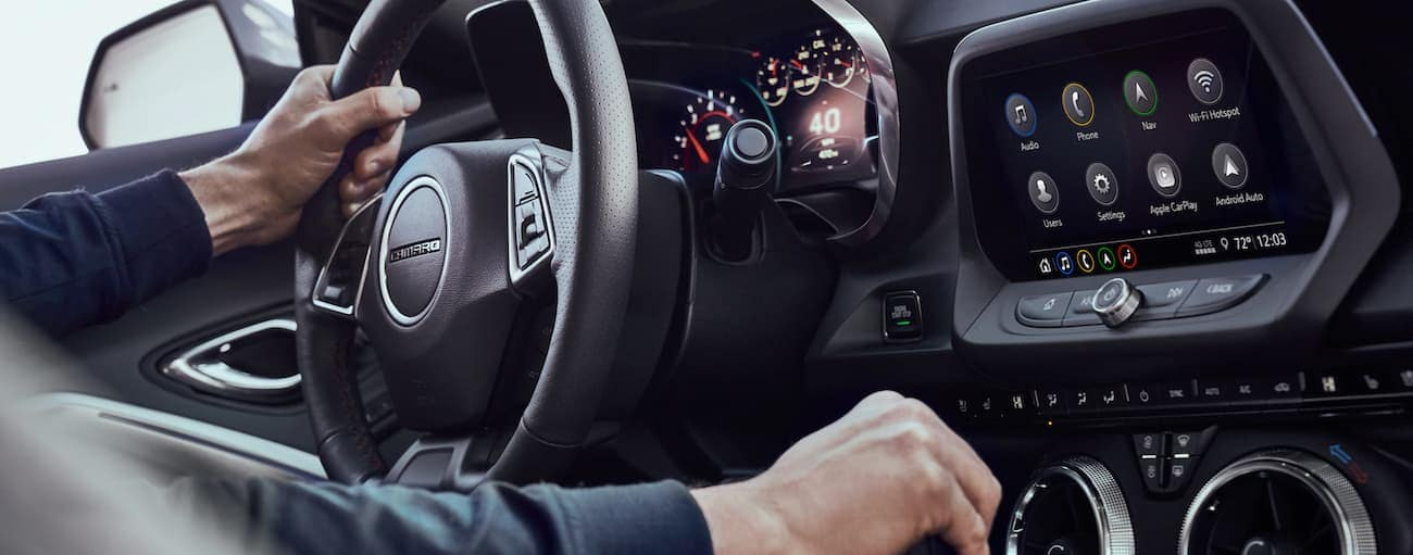 A closeup shows a driver's hands on the shifter and wheel inside a 2021 Chevy Camaro.