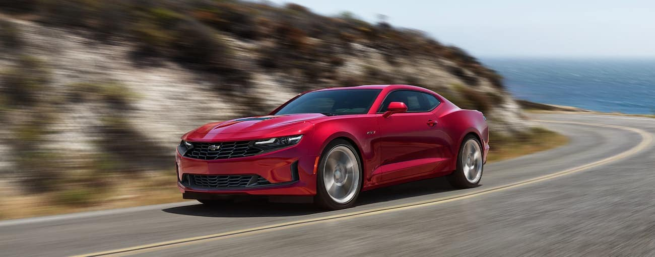 A red 2021 Chevy Camaro is driving past the ocean around a corner with a dune after winning the 2021 Chevy Camaro vs 2021 Ford Mustang comparison.