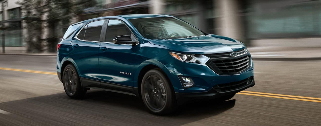 A blue 2021 Chevy Equinox Sport is driving on a city street.