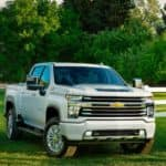 A popular Chevy diesel truck, a white 2021 Chevy Silverado 2500HD is parked on the grass next to a white fence.