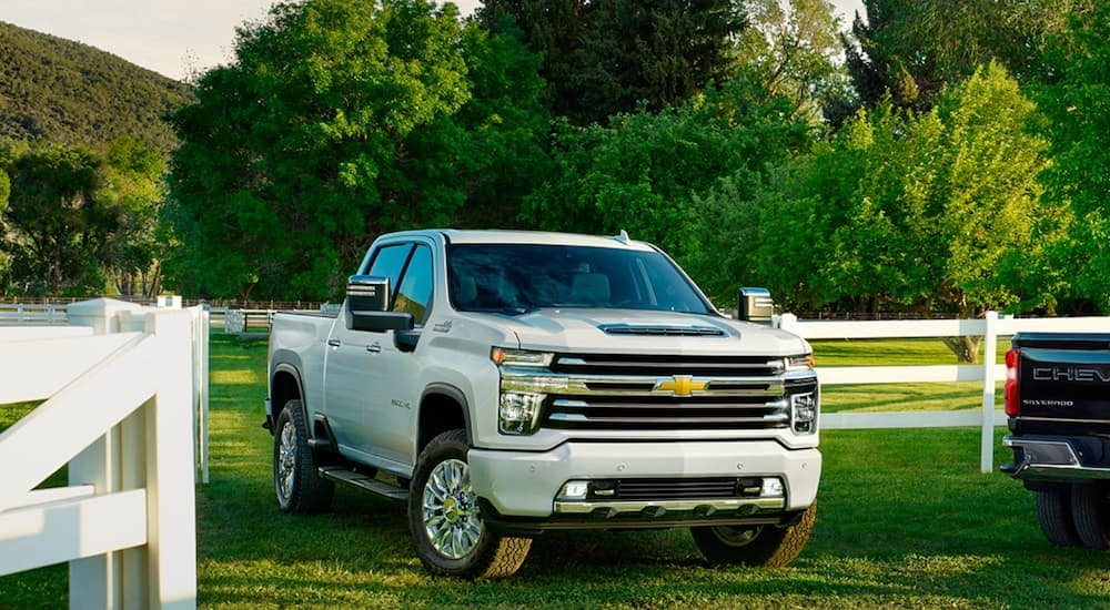 A popular Chevy diesel truck, a white 2021 Chevy Silverado 2500HD, is parked on the grass next to a white fence.