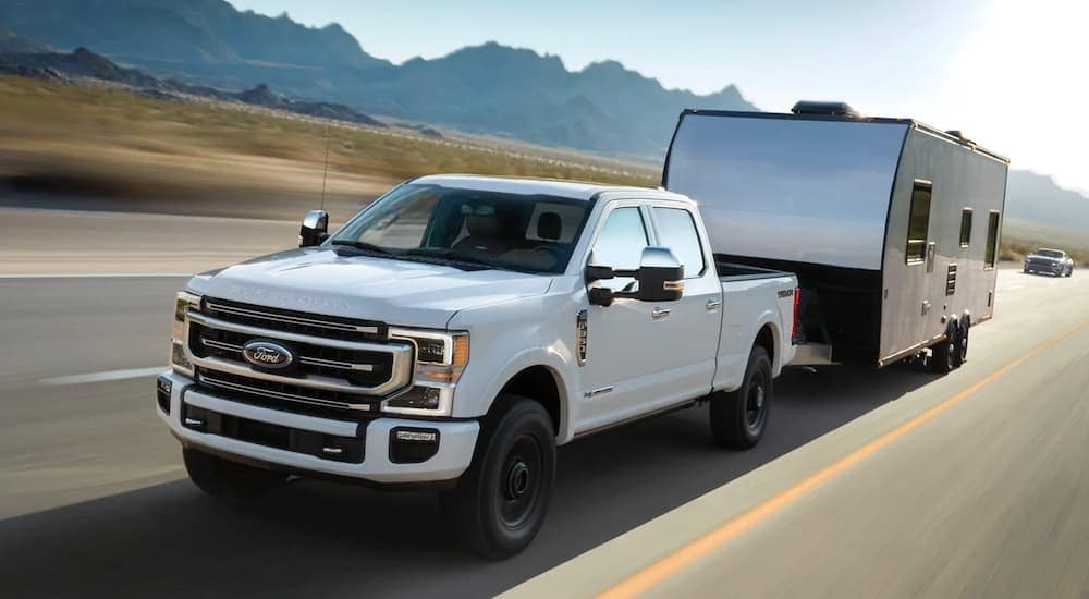 A white 2021 Ford F-350 Tremor is towing a trailer down the highway.