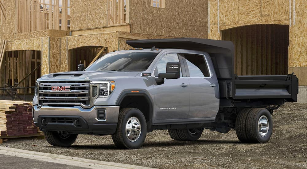 A grey 2021 GMC Sierra 3500HD is parked with an unfinished house in the background.