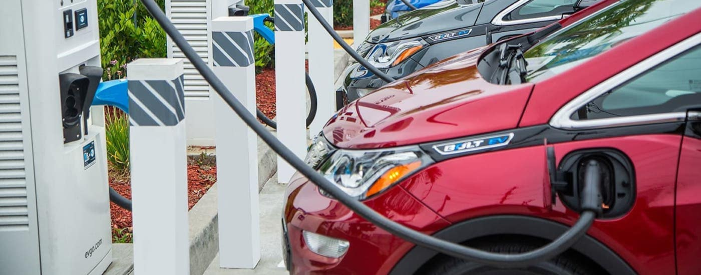 A row of Chevy EVs are charging at a charging station.