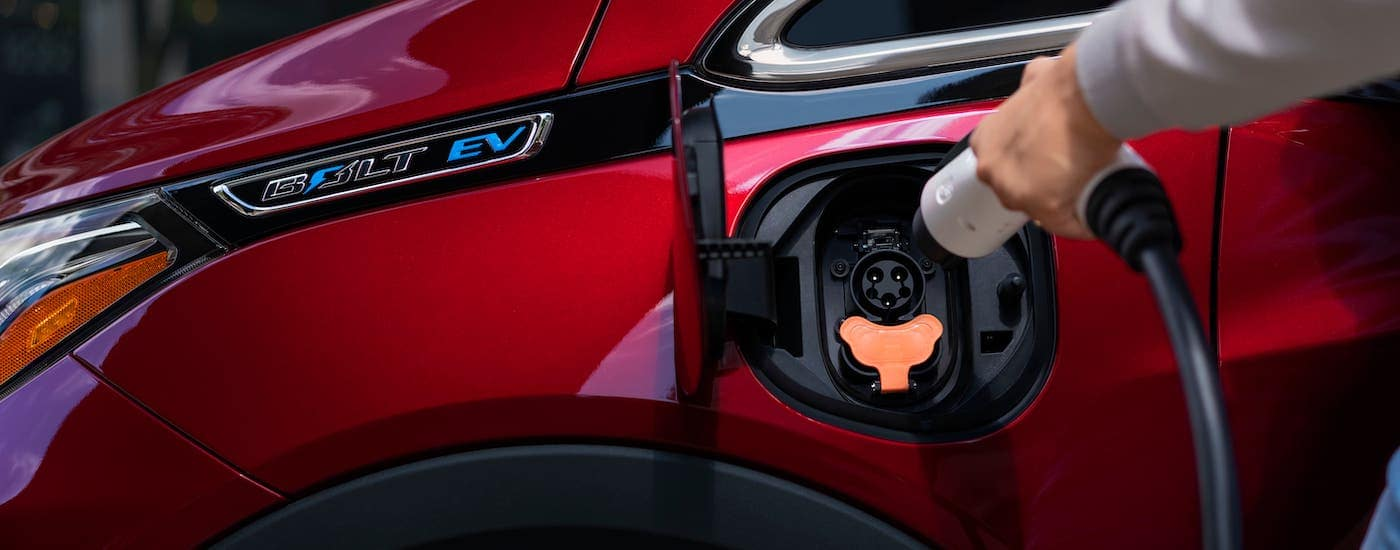 A closeup shows a hand plugging in a red 2020 Chevy Bolt EV.