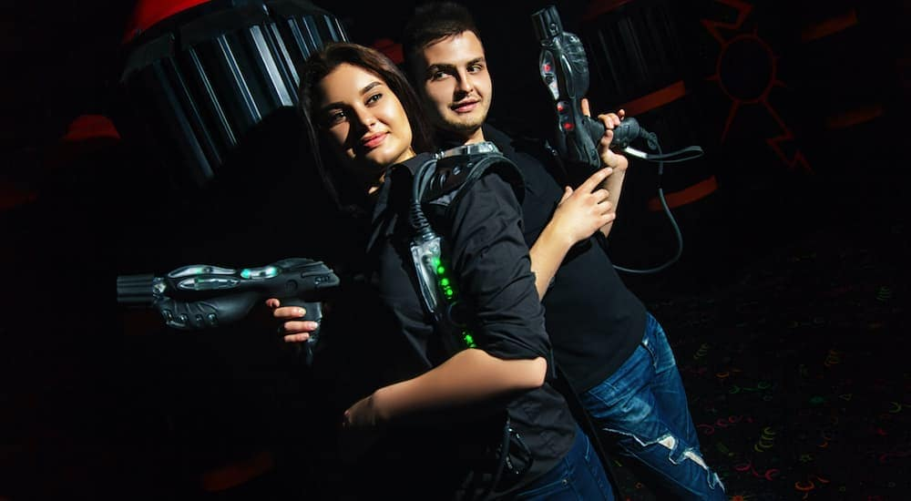 A man and woman are standing back to back holding up laser tag guns.