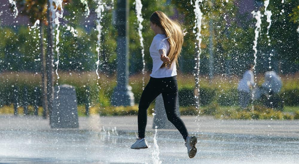 A young girl is playing in the sprinklers in a town park.