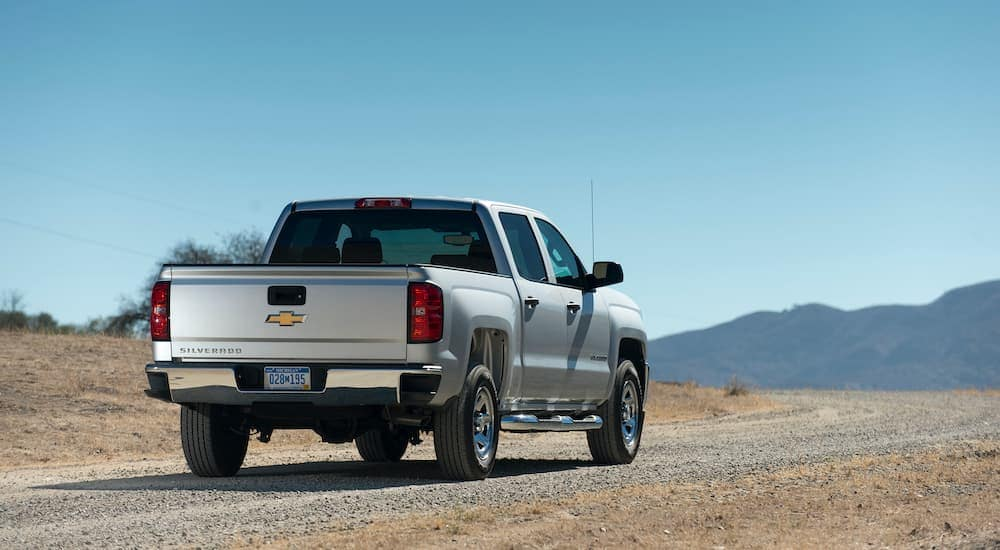 A silver 2017 Chevy Silverado is parked in the dirt, shown from behind and angled right.