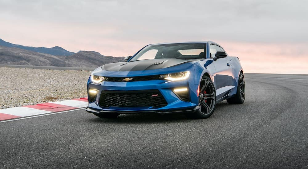 A black and blue 2017 Chevy Camaro SS 1LE is driving around the track after leaving a used car dealership near you.