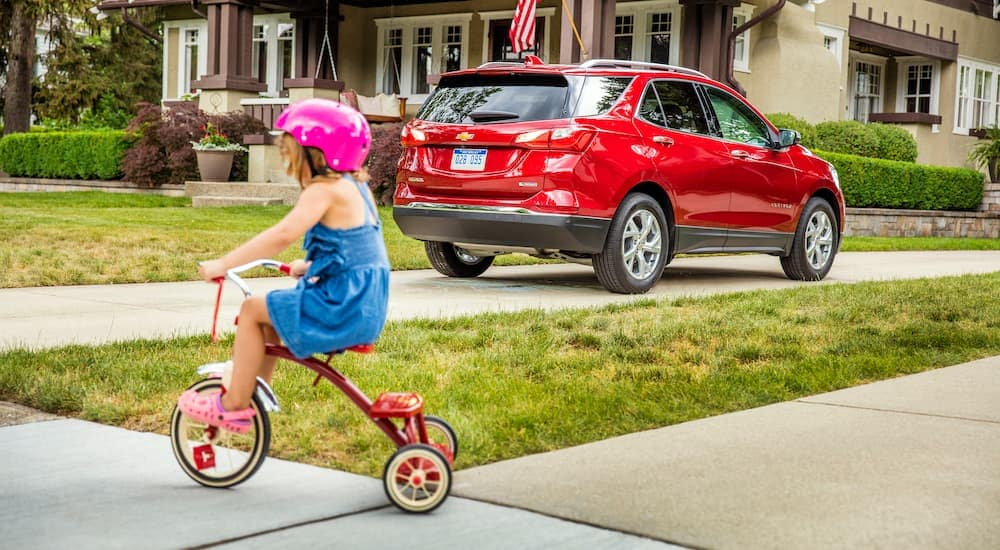 A red 2018 Chevy Equinox is parked in a driveway with a child on a tricycle behind it.