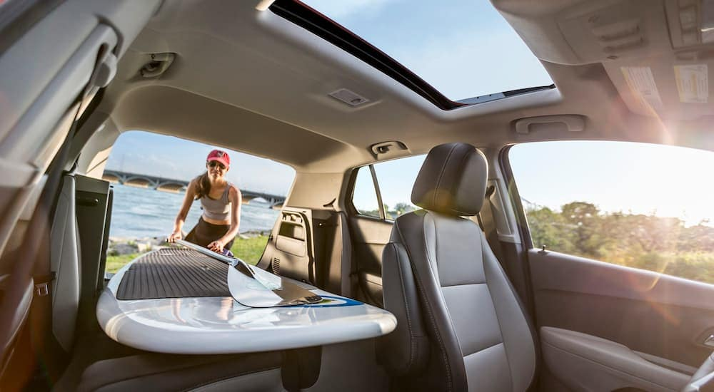 The grey interior is shown on a 2016 Chevy Trax LTZ with a surfboard being loaded in the trunk.