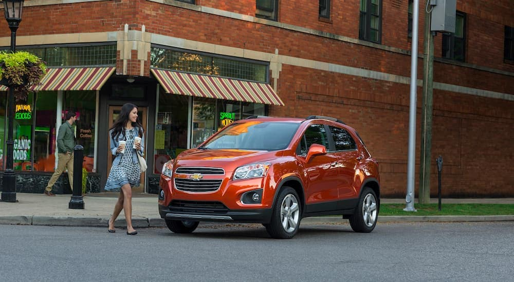 A popular used SUV for sale, an orange 2016 Chevy Trax, is parked outside of a natural food store.