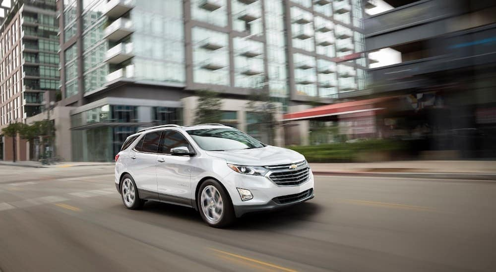 A white 2018 Chevy Equinox is driving through the city.