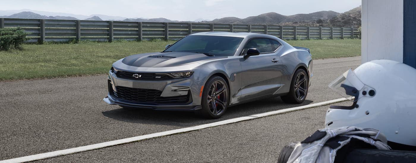 grey 2021 Chevy Camaro 2SS is parked on a racetrack with a white racing helmet in the foreground.