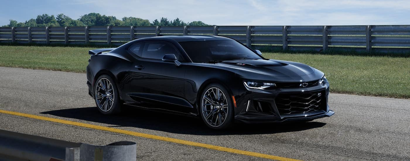 A black 2021 Chevy Camaro ZL1 is parked on tarmac with a guardrail in the background.
