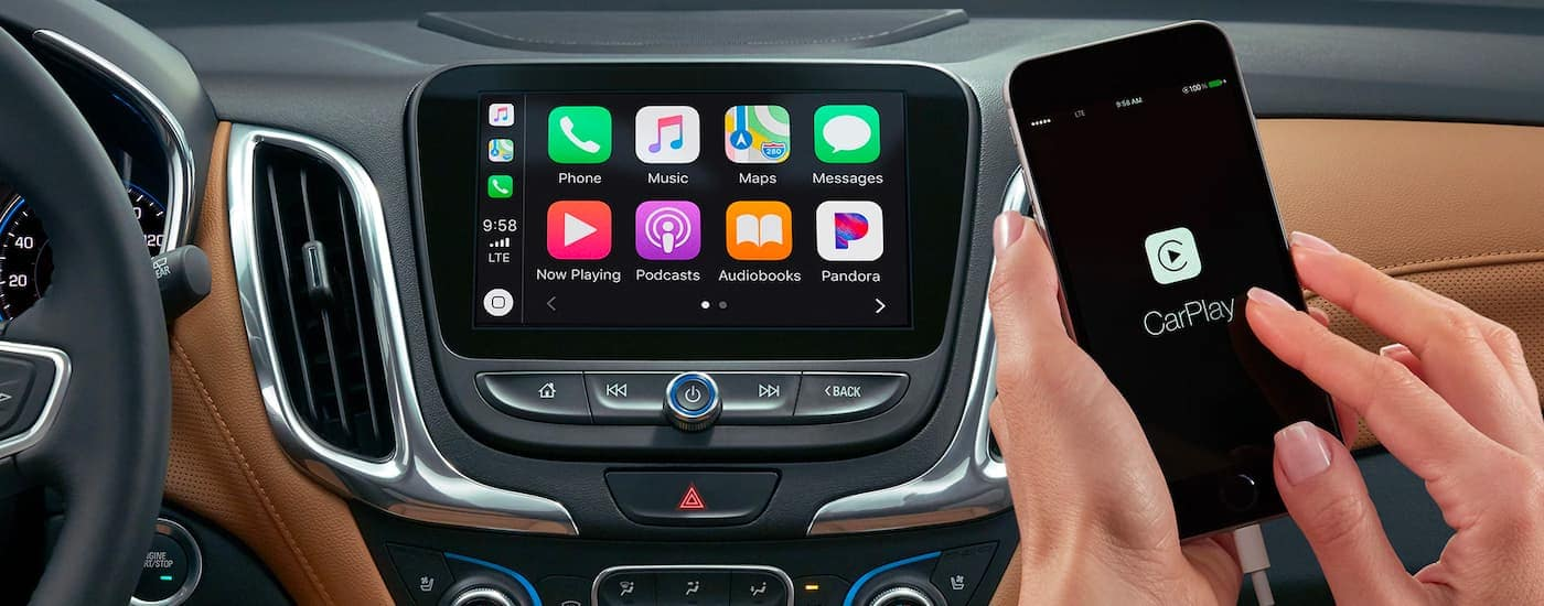 A close up is shown of a phone using car play and the infotainment screen with apps on a 2021 Chevy Equinox.