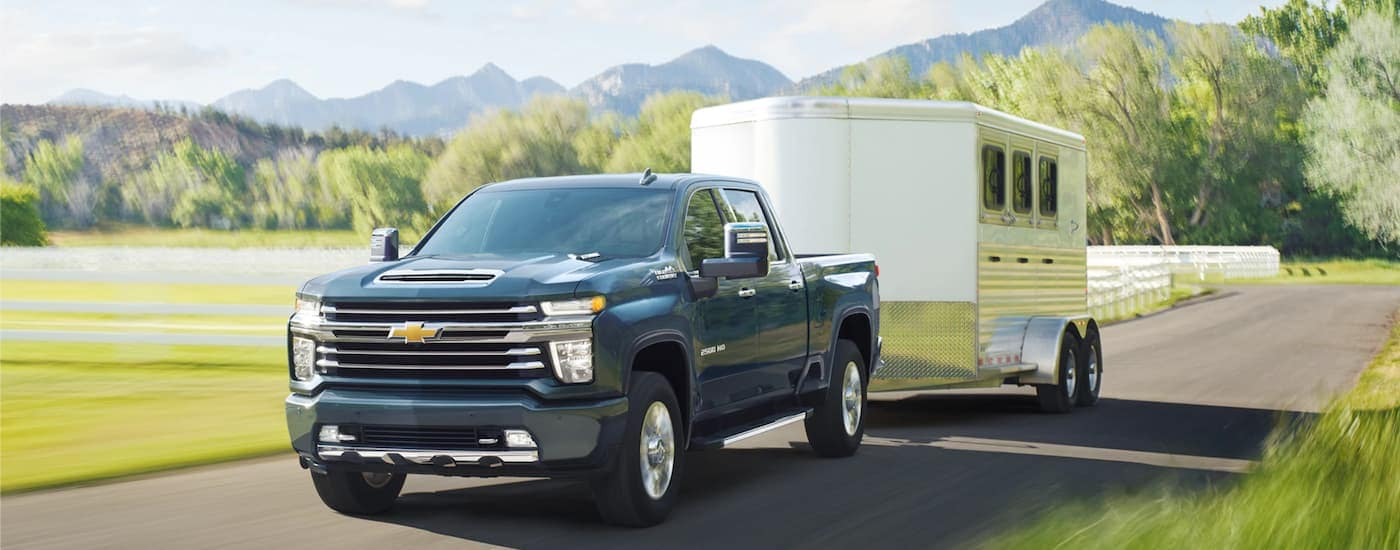 A black 2021 Chevy Silverado 2500 HD is towing a trailer past a field and white fence.