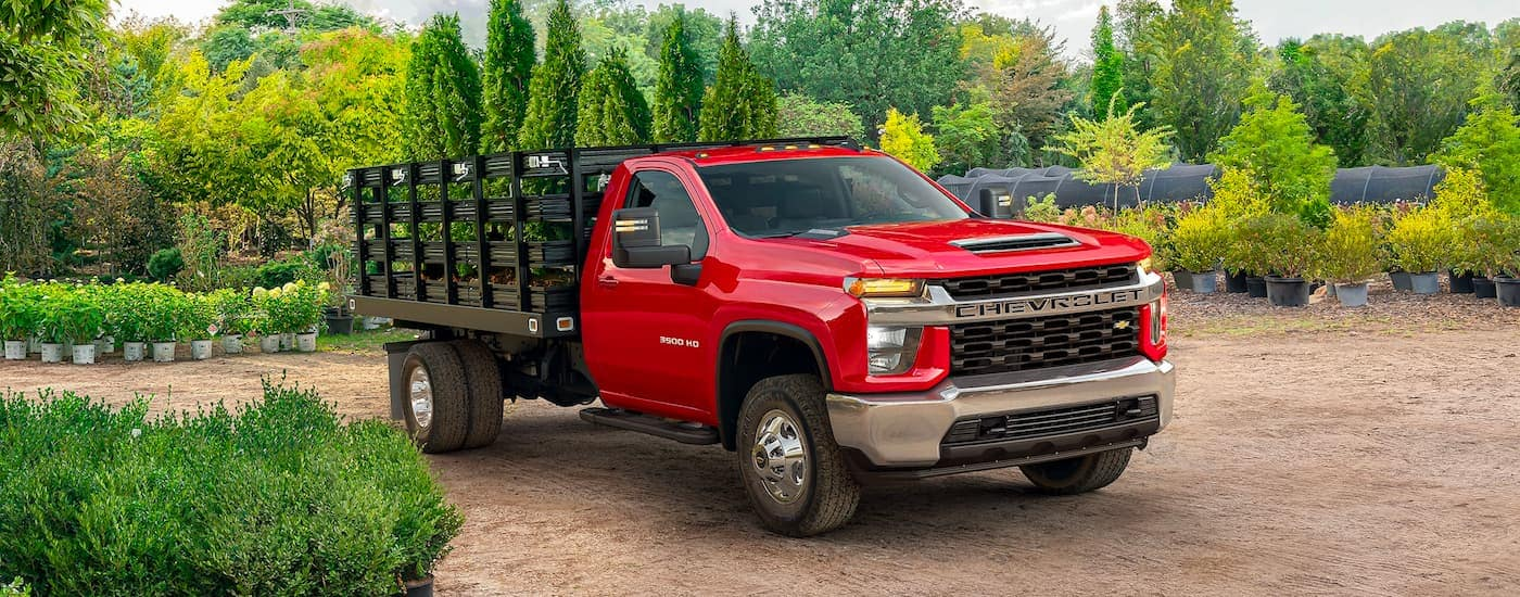 A red 2021 Chevy Silverado 3500 HD is shown parked in a plant nursery.