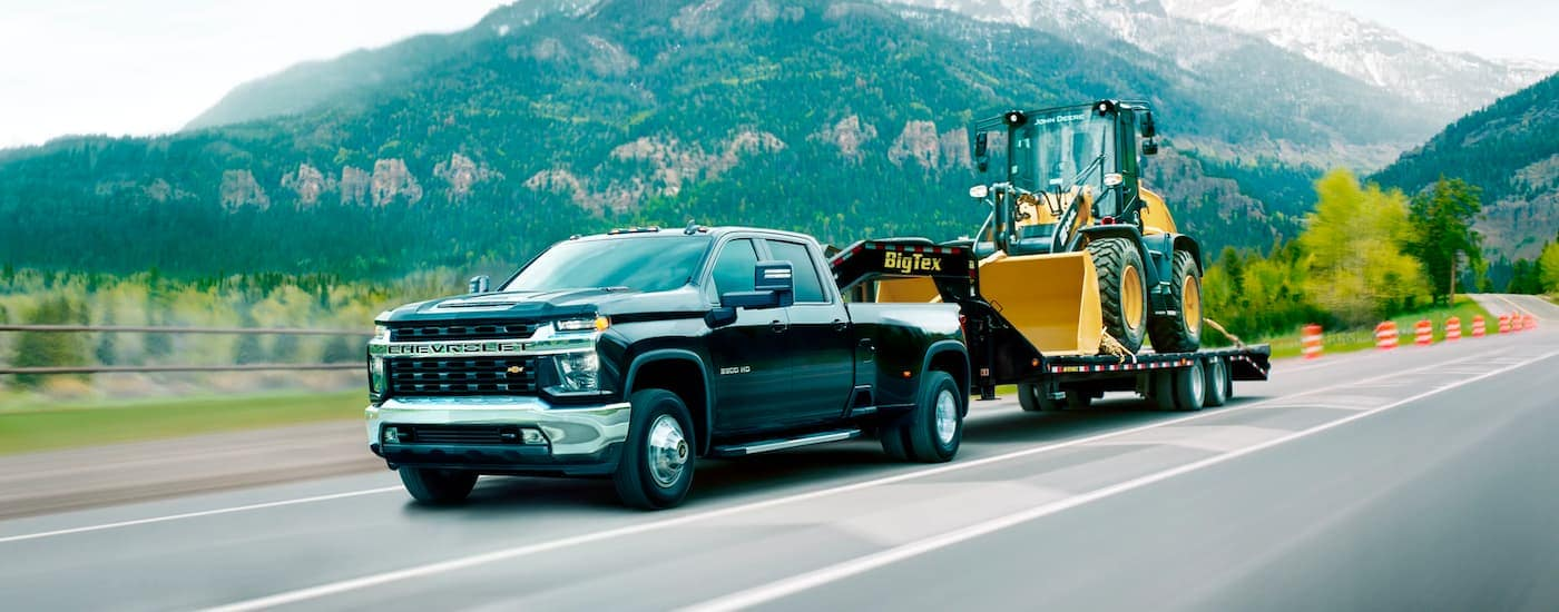 A black 2021 Chevy Silverado 3500 HD is shown towing a front loader on a trailer down the highway.
