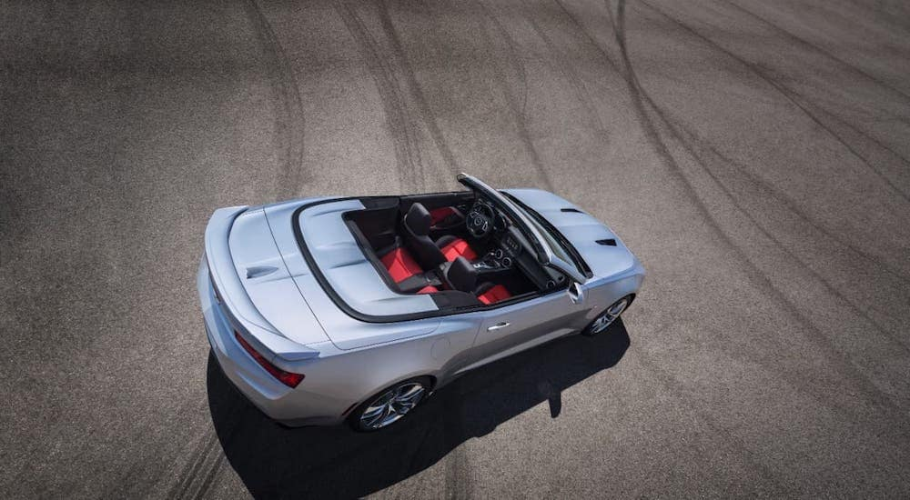 A silver 2021 Chevy Camaro convertible is shown from a high angle in an empty lot.