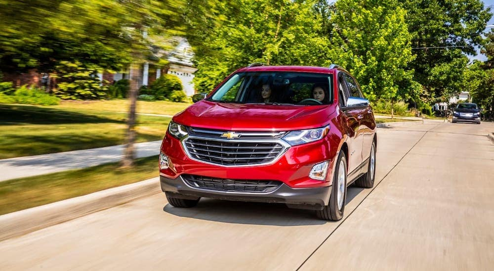 A red 2021 Chevy Equinox is driving on a suburban street after leaving a car dealer in Buford, GA.