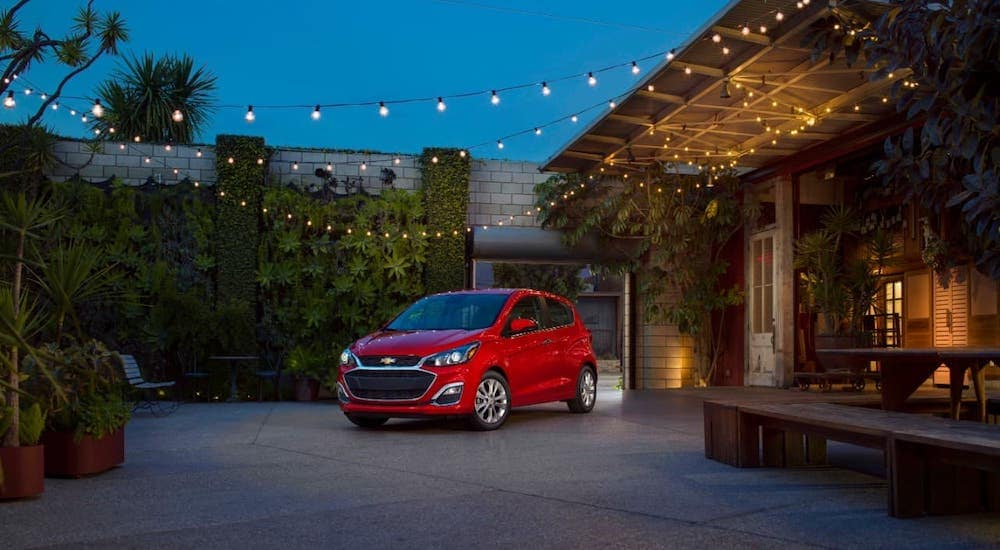 A red 2021 Chevy Spark is parked under string lights.