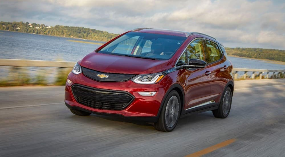 A red 2020 Chevy Bolt is driving past a lake.