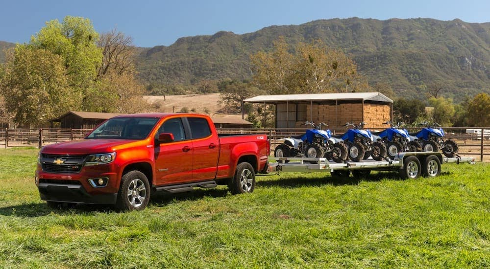 A red 2016 Chevy Colorado is towing four wheelers.