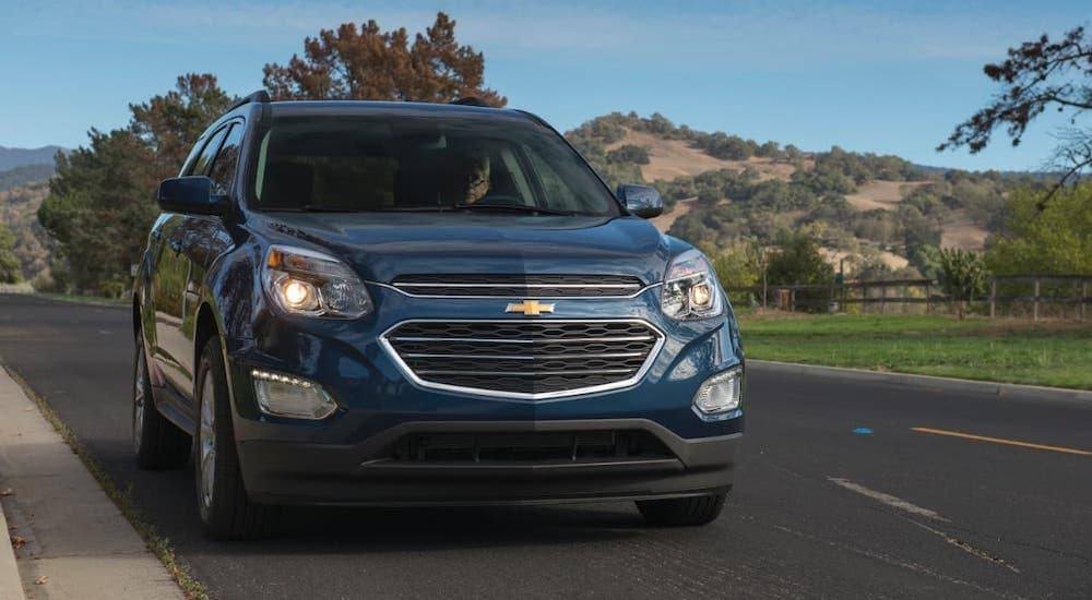 A blue 2016 Chevy Equinox is driving on a highway in front of distant mountains.